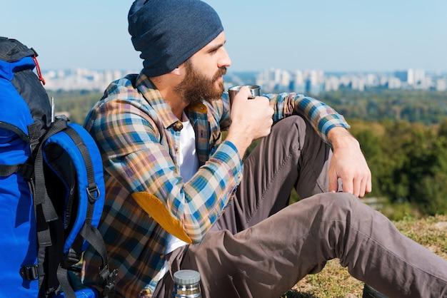Tijd om te ontspannen. knappe jongeman zit in de buurt van rugzak en kijkt weg terwijl hij drinkt