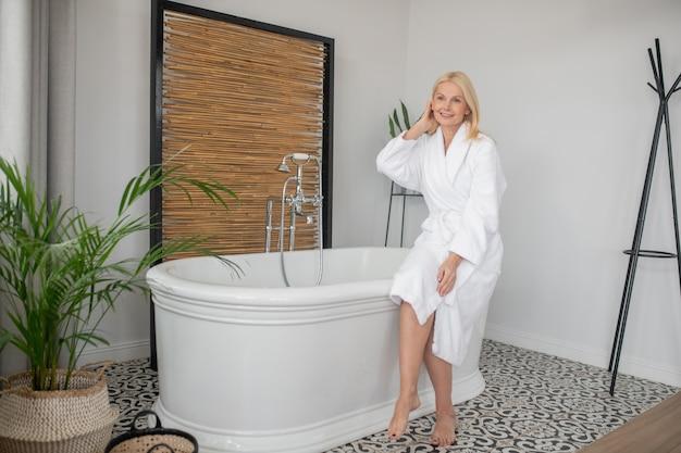 Tijd om te ontspannen. vrouw in een witte badjas die een bad wil nemen