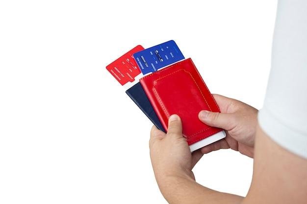 Tijd om te reizen. de kerel houdt vliegtickets en paspoorten in handen die op wit worden geïsoleerd