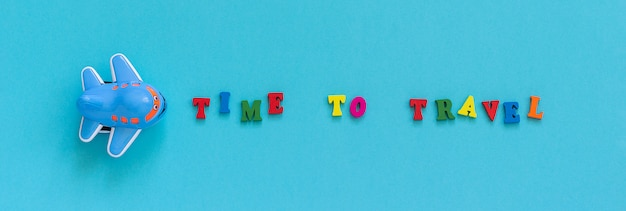 Tijd om te reizen en het grappige speelgoedvliegtuig van kinderen op blauwe document achtergrond