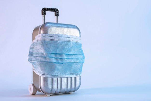 Tijd om te reizen. het concept van veilige rust tijdens een pandemie covid-19 coronavirus. koffer voor op reis met een medisch masker.
