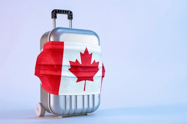 Tijd om te reizen. het concept van veilige rust tijdens een pandemie covid-19 coronavirus. koffer voor reizen met een medisch masker en vlag van canada.