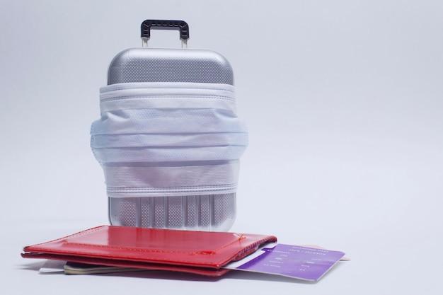Tijd om te reizen. het concept van veilige rust tijdens een pandemie covid-19 coronavirus. koffer voor reizen met een medisch masker en vliegtickets met een paspoort.
