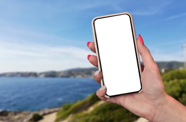 Tijd om te reizen. smartphone in de hand, tegen de achtergrond van de zee en de stad onder een zonnige hemel.
