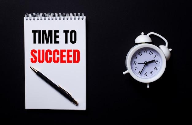 Tijd om te slagen is geschreven in een wit notitieblok in de buurt van een witte wekker op een zwarte achtergrond.