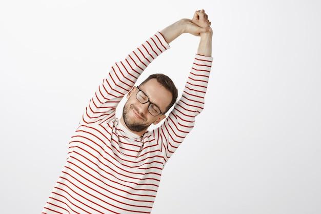 Tijd om te sporten voor een gezond lichaam. portret van moe en tevreden aantrekkelijke man met varkenshaar in zwarte brillen, die zich uitstrekt met opgeheven handen en naar rechts kantelt