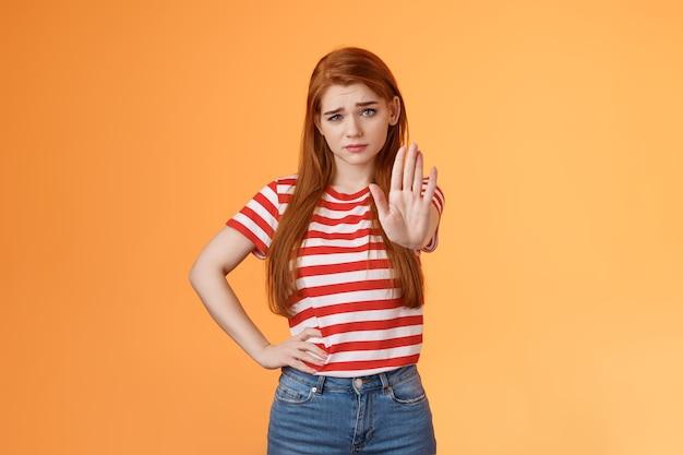 Tijd om te stoppen met serieus kijken ontevreden bazig zelfverzekerd roodharig meisje strek arm uit in verbod verbied...