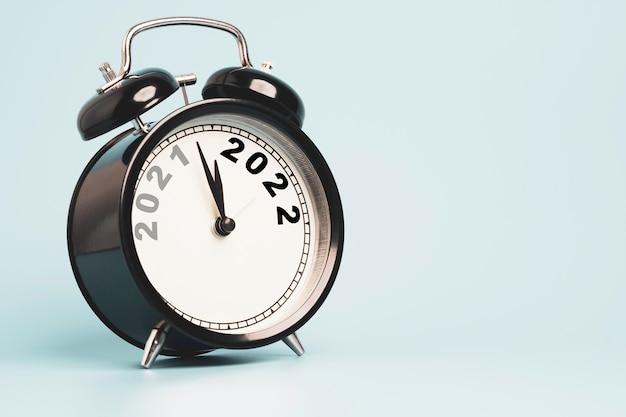 Tijd om te veranderen van 2021 naar 2022 printscherm op klok met blauwe achtergrond