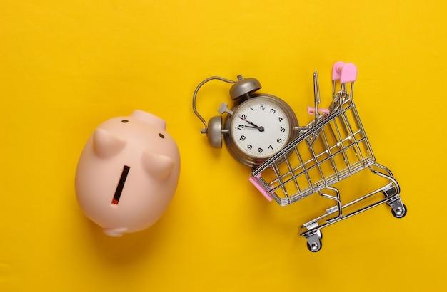 Tijd om te winkelen, kerstinkopen. spaarvarken en supermarktkarretje met retro wekker op geel