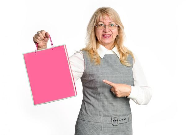 Tijd om te winkelen. rijpe vrouw toont haar vinger op het roze pakket