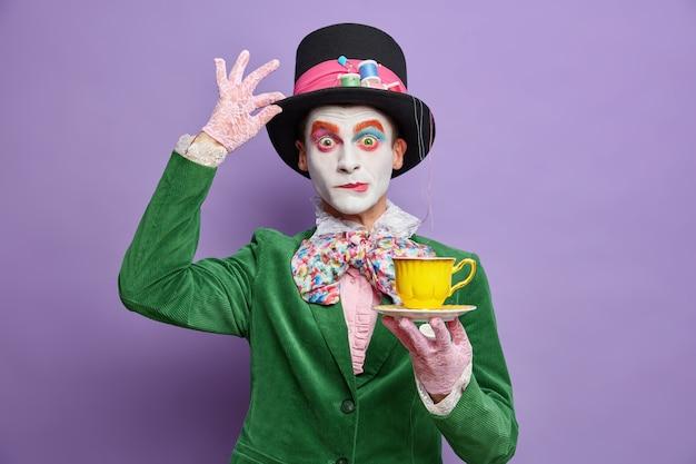 Tijd om thee te drinken. aristocratische heer met lichte make-up heeft afbeelding van fictief personage houdt kopje drank draagt grote hoed heeft zich afgevraagd uitdrukking vormt over paarse muur