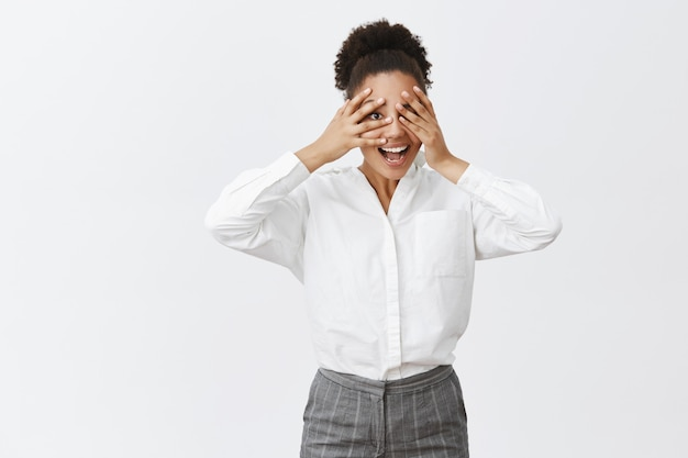 Tijd om verstoppertje te spelen. portret van vrolijke aantrekkelijke en grappige donkere vrouwelijke ondernemer met plezier, kinderachtig en zorgeloos zijn tijdens het spelen van kiekeboe, gluren door de vingers en glimlachen