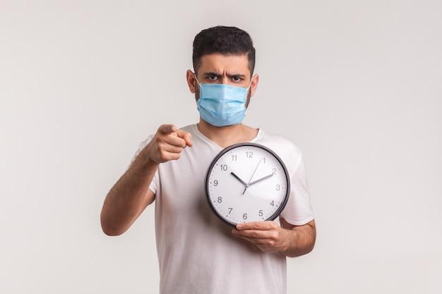 Tijd om voorzichtig te zijn! man in beschermend hygiënisch masker met klok, waarschuwing voor nieuwe virusepidemie
