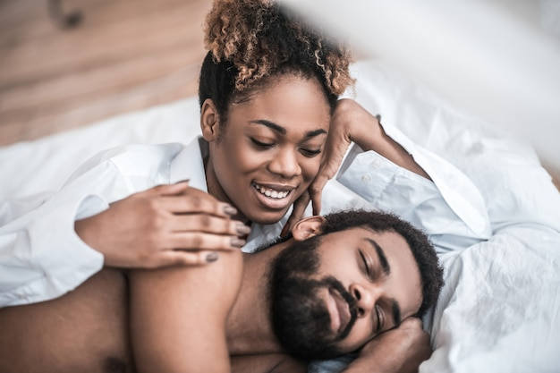 Tijd om wakker te worden. jonge volwassen gelukkig donkere vrouw hand aanraken van bebaarde man in bed te raken