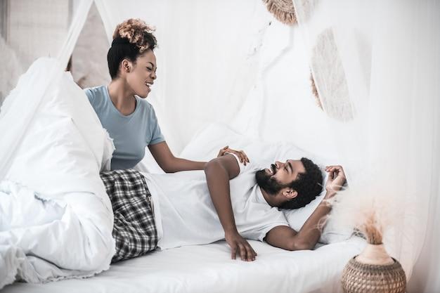 Tijd om wakker te worden. vrolijke vergadering donkere huid vrouw deken nemen van slaperige man thuis in de slaapkamer liggen