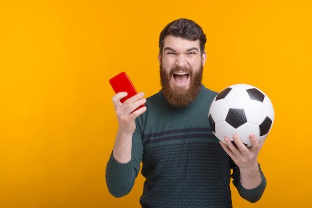 Tijd om wat voetbal en voetbal aan de telefoon te kijken! opgewonden man houdt een telefoon en een bal in zijn handen schreeuwen op gele ruimte.