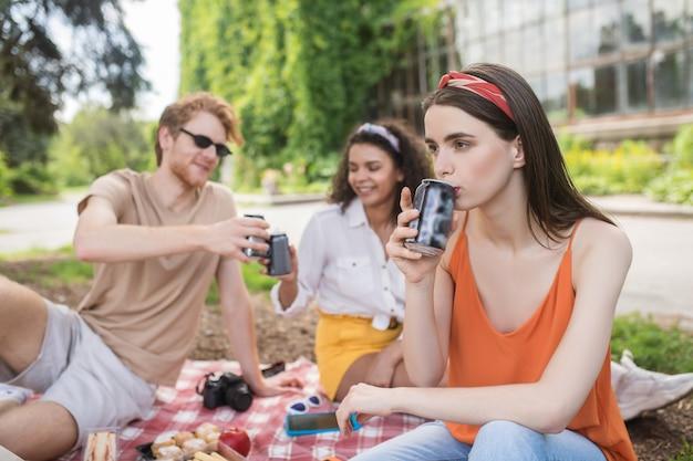 Tijd ontspannen. jonge langharige peinzende meid die een drankje drinkt en vrolijke vrienden die achterop kletsen op een picknick in het park