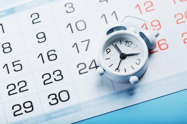 Tijd op een witte wekker liggend op de kalender en een blauwe achtergrond.