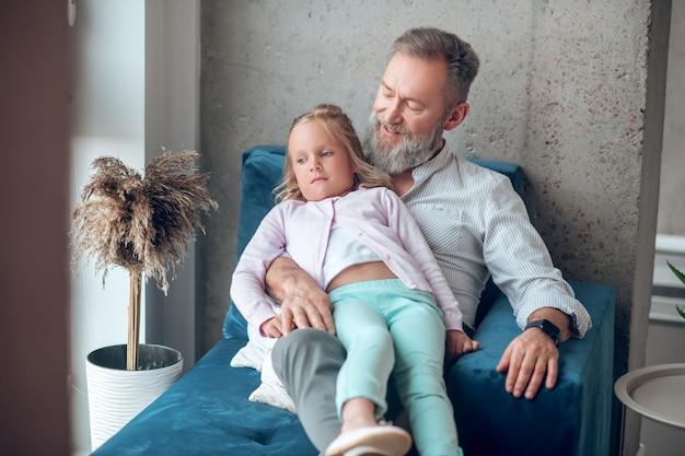 Tijd samen. een volwassen man zit bij het raam met zijn dochter