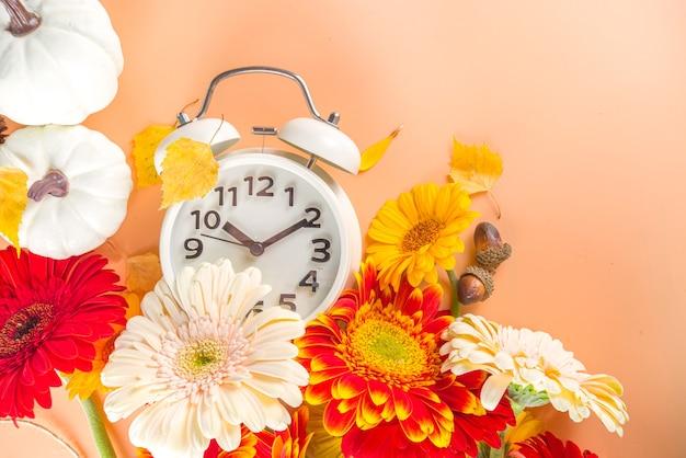 Tijd terug vallen. zomertijd eindigt. winter herfsttijd met wekker, pompoenen, gerbera, bladeren