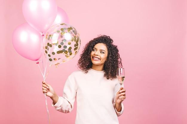 Tijd voor een feestje! gelukkig mooie afro-amerikaanse vrouw met glas champagne, ballonnen en vallende confetti geïsoleerd op roze achtergrond.
