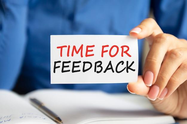 Tijd voor feedback is geschreven op een wit visitekaartje in de hand van een vrouw. blauwe achtergrond. bedrijfs- en reclameconcept
