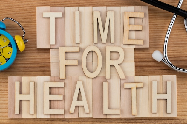 Tijd voor gezondheid - tekst in vintage letters op houten blokken met stethoscoop en wekker. geneeskunde concept.