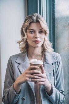 Tijd voor jezelf. mooie zakelijke blonde vrouw in grijze jas koffie houden in haar handen kalm rusten in de buurt van venster in kantoor