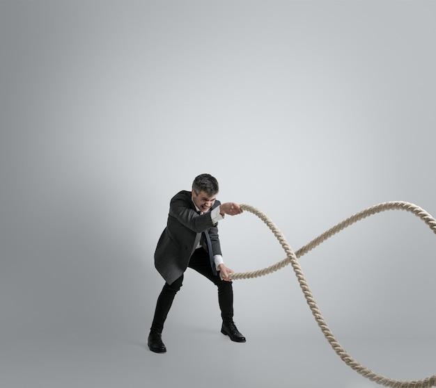 Tijd voor kracht. man in kantoorkleding training met touwen op grijze achtergrond