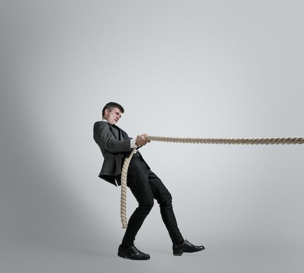 Tijd voor kracht. man in kantoorkleding training met touwen op grijze muur. krijg een doel, het overwinnen van problemen, deadlines. zakenman in beweging, actie. sport, gezonde levensstijl, werken.