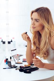 Tijd voor lippenstift. zijaanzicht van een mooie jonge vrouw die lippenstift aanbrengt en naar haar spiegelbeeld kijkt terwijl ze aan de kaptafel zit
