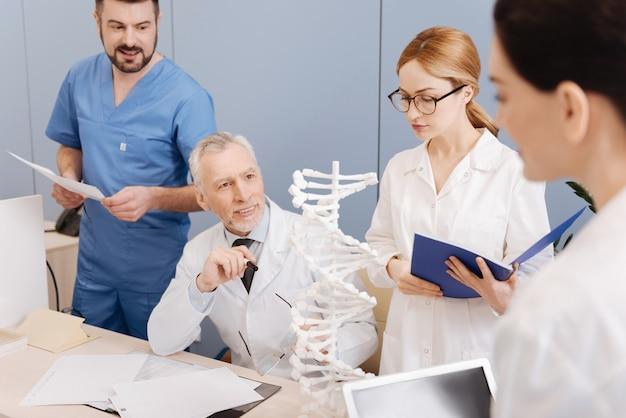 Tijd voor onderzoek. geïnteresseerde vrolijke slimme mentor die werkt en de klas heeft in de medische universiteit terwijl hij luistert naar rapporten van de studenten over de dna-structuur
