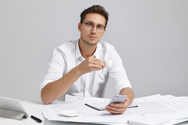 Tijd voor pauze. baan, ontspanning en moderne elektronische apparaten. succesvolle professionele hoofdingenieur surfen op internet op mobiele telefoon en genieten van espresso, rust tijdens werkdag op kantoor