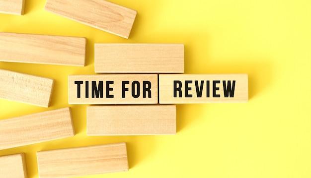 Tijd voor review tekst geschreven op een houten blokken op een gele achtergrond.