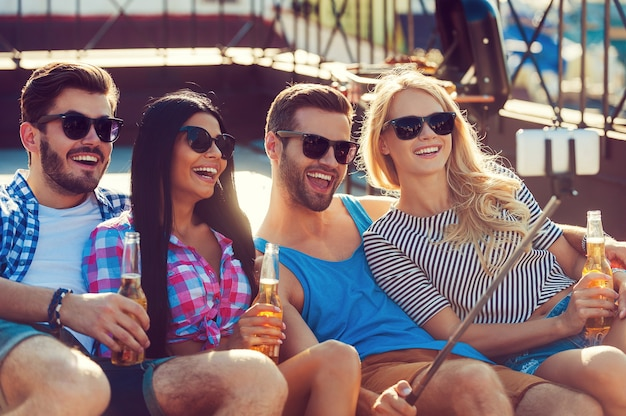 Tijd voor selfies! groep gelukkige jonge mensen die zich aan elkaar hechten en selfie maken op smartphone terwijl ze plezier hebben op het dak