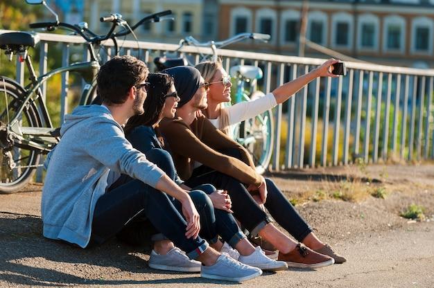 Tijd voor selfies. groep jonge lachende mensen die zich aan elkaar hechten en selfie maken via een smartphone terwijl ze buiten zitten samen met fietsen op de achtergrond