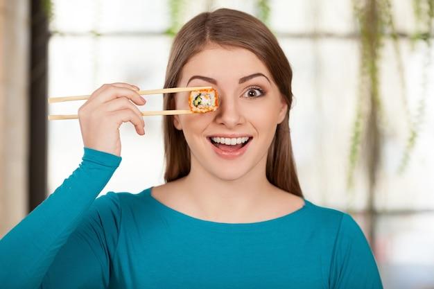 Tijd voor sushi! mooie jonge vrouw die sushi voor haar oog houdt en glimlacht terwijl ze in het restaurant zit