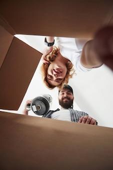 Tijd voor uitpakken. gelukkig paar samen in hun nieuwe huis. conceptie van verhuizen