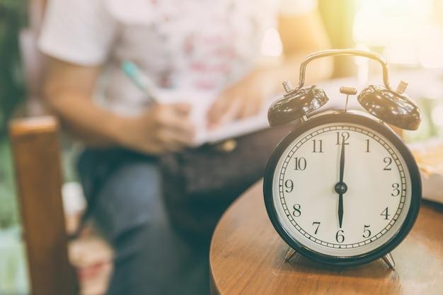 Tijd voor werkconcept. klok getimed om 8 uur met achtergrond van werkende mensen vervagen.