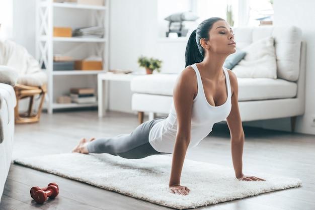 Tijd voor yoga. aantrekkelijke en gezonde jonge vrouw die oefeningen doet terwijl ze thuis rust