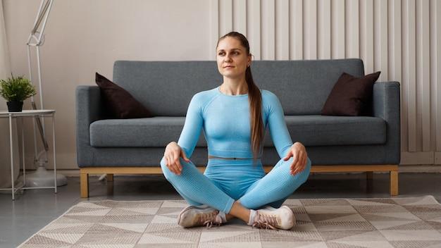 Tijd voor yoga. aantrekkelijke jonge vrouw die en in yogapositie uitoefent terwijl thuis rust