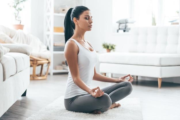 Tijd voor yoga. aantrekkelijke jonge vrouw die traint en in yoga lotuspositie zit terwijl ze thuis rust