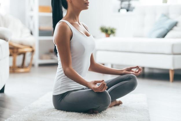 Tijd voor yoga. close up van aantrekkelijke jonge vrouw die traint en in yoga lotuspositie zit terwijl ze thuis rust