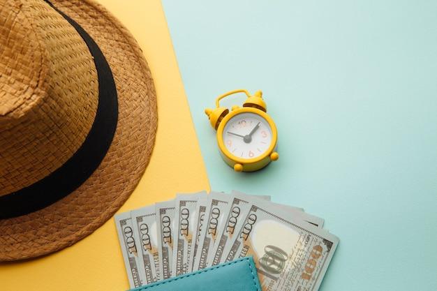 Tijd voor zomervakantie. hoed en paspoort met geldbankbiljetten op geel blauw oppervlak