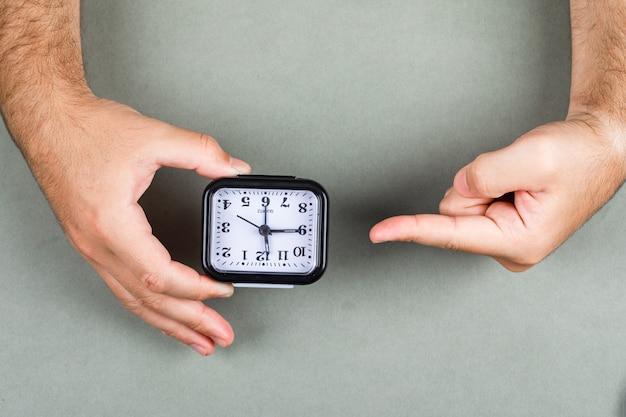Tijdbeheer en kloktikend concept met klok op grijze hoogste mening als achtergrond. handen houden en wijzen naar de klok. horizontaal beeld