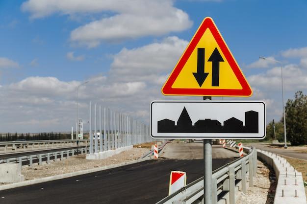 Tijdelijk verkeersbord tweerichtingsverkeer en verkeersbord het begin van het dorp tegen de lucht en de weg in aanbouw.