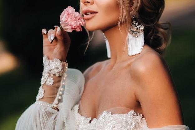Tijden in de hand van een vrouw, neemt ze een roos, bruidsprijs, ochtendbruid, witte jurk, doet oorbellen aan.