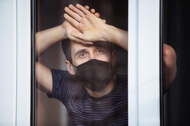Tijdens de quarantaine blijft een man geïsoleerd thuis. coronapandemie. de man kijkt uit het raam de straat in
