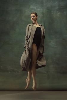 Tijdens de vlucht. sierlijke klassieke ballerina dansen, poseren geïsoleerd op donkere studio achtergrond. stijlvolle trenchcoat. genade, beweging, actie en bewegingsconcept. ziet er gewichtloos, flexibel uit. in de mode.