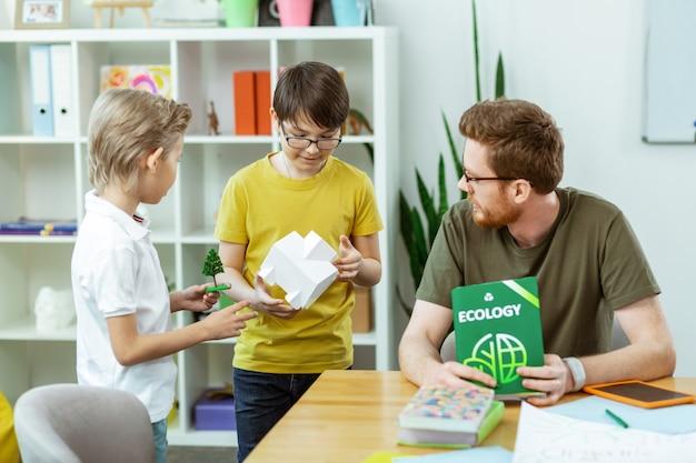 Tijdens ecologielessen. nieuwsgierige jongens die stukjes plastic model vasthouden terwijl de leraar hen vertelt over de natuur
